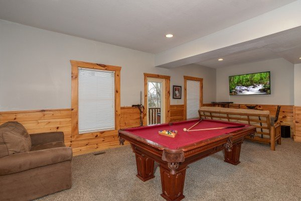 Game room with pool table, futons, and TV at The Cowboy Way, a 4 bedroom cabin rental located in Pigeon Forge