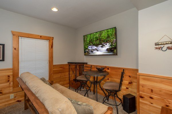 TV and bistro set in the game room at The Cowboy Way, a 4 bedroom cabin rental located in Pigeon Forge
