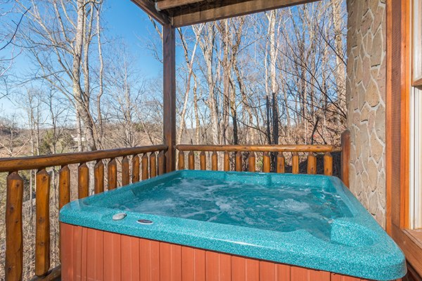 Hot tub on a covered deck at The Cowboy Way, a 4 bedroom cabin rental located in Pigeon Forge