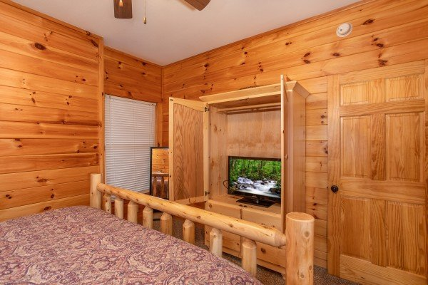 Armoire and TV in the downstairs king bedroom at The Cowboy Way, a 4 bedroom cabin rental located in Pigeon Forge