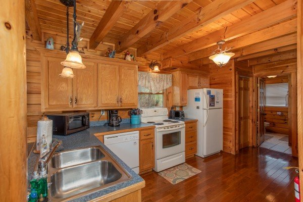 Kitchen with white appliances at The Cowboy Way, a 4 bedroom cabin rental located in Pigeon Forge