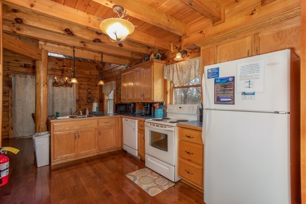 Kitchen with white appliances and pass through to the dining space at The Cowboy Way, a 4 bedroom cabin rental located in Pigeon Forge