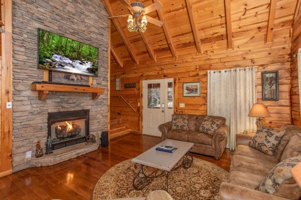 Fireplace and TV in the living room at The Cowboy Way, a 4 bedroom cabin rental located in Pigeon Forge