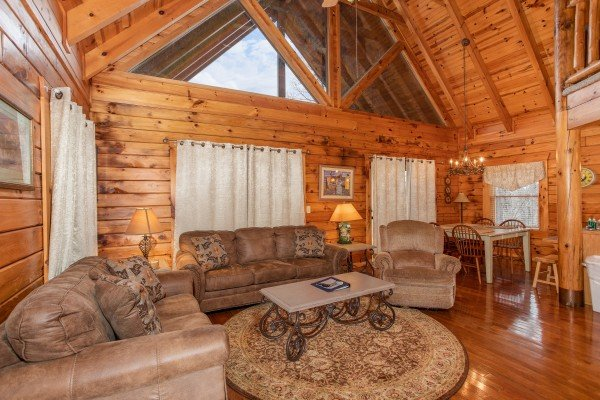 Living room seating and dining room table for four at The Cowboy Way, a 4 bedroom cabin rental located in Pigeon Forge