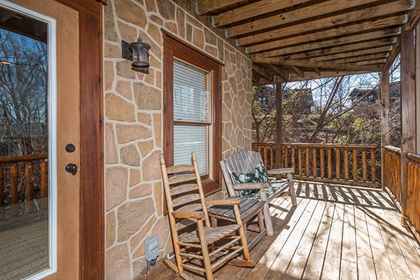 Rocking chair and bench on the lower deck at The Cowboy Way, a 4 bedroom cabin rental located in Pigeon Forge
