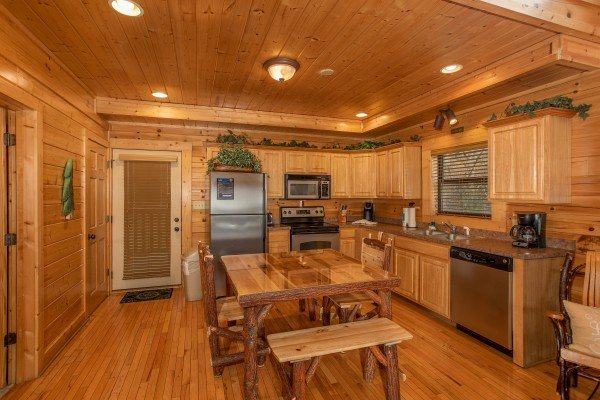 Dining table for six and kitchen with stainless appliances at Let the Good Times Roll, a 2 bedroom cabin rental located in Pigeon Forge