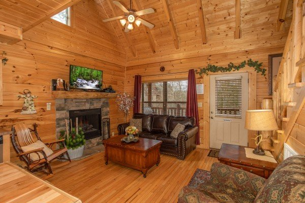 Living room with fireplace and TV at Let the Good Times Roll, a 2 bedroom cabin rental located in Pigeon Forge