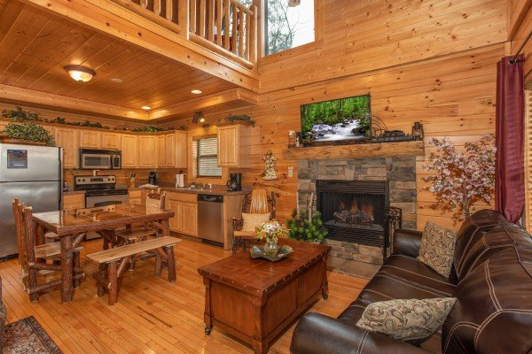 Living room, dining room, and kitchen at Let the Good Times Roll, a 2 bedroom cabin rental located in Pigeon Forge
