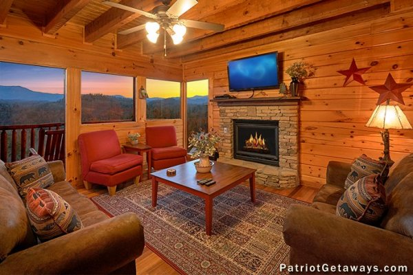 Living room with fireplace, TV, and sunset views at The Big View, a 4 bedroom cabin rental located in Pigeon Forge