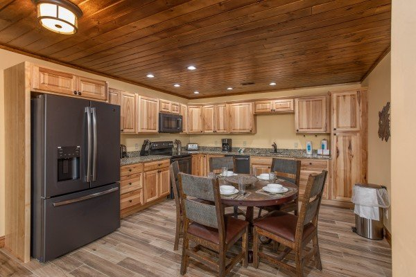 Dining space for four and kitchen with stainless appliances at Over Ober Lodge, a 5 bedroom cabin rental located in Gatlinburg