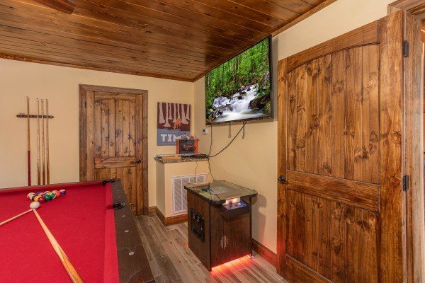 Arcade game and large TV in the game room at Over Ober Lodge, a 5 bedroom cabin rental located in Gatlinburg