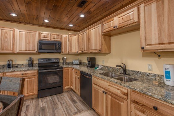 Kitchen with black appliances at Over Ober Lodge, a 5 bedroom cabin rental located in Gatlinburg