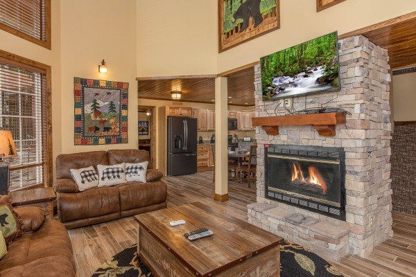 Stone fireplace and TV at Over Ober Lodge, a 5 bedroom cabin rental located in Gatlinburg
