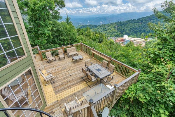 Large lower deck with dining space and rocking chairs at Over Ober Lodge, a 5 bedroom cabin rental located in Gatlinburg