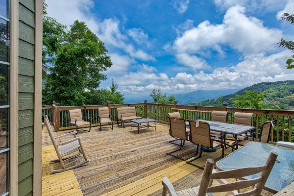 Chairs, rocking chairs, and dining table on the deck at Over Ober Lodge, a 5 bedroom cabin rental located in Gatlinburg