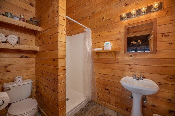 Bathroom with a shower stall and pedestal sink at Country Getaway, a 1 bedroom cabin rental located in Pigeon Forge