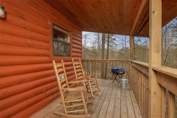 Deck with rocking chairs and a charcoal grill at Country Getaway, a 1 bedroom cabin rental located in Pigeon Forge