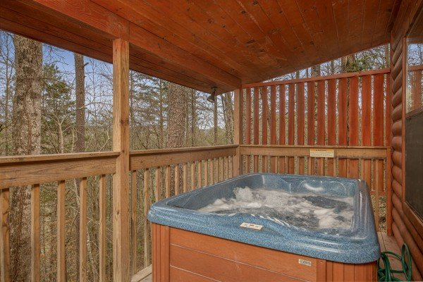 Hot tub on a covered porch with privacy fence at Country Getaway, a 1 bedroom cabin rental located in Pigeon Forge