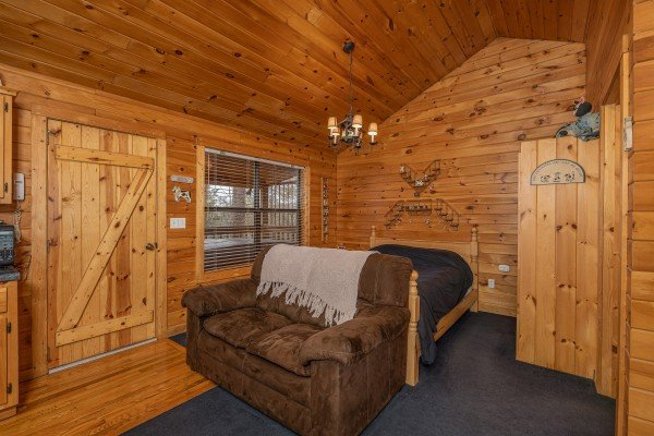Loveseat and bed at Country Getaway, a 1 bedroom cabin rental located in Pigeon Forge