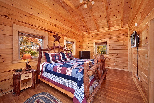 king sized log bed with tv mounted to wall at foot of bed at looky yonder a 2 bedroom cabin rental located in gatlinburg