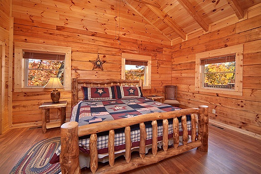 king sized log bed in bedroom at looky yonder a 2 bedroom cabin rental located in gatlinburg