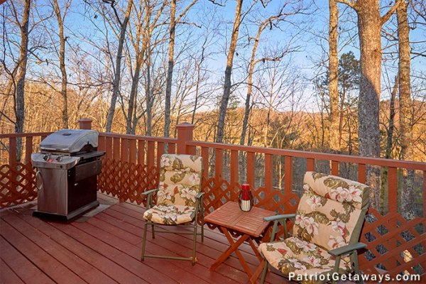 A propane grill and two chairs near a table on the deck at Elevation 1454, a 1-bedroom cabin rental located in Pigeon Forge