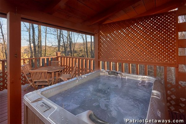 Hot tub with wooed views and a privacy fence at Elevation 1454, a 1-bedroom cabin rental located in Pigeon Forge