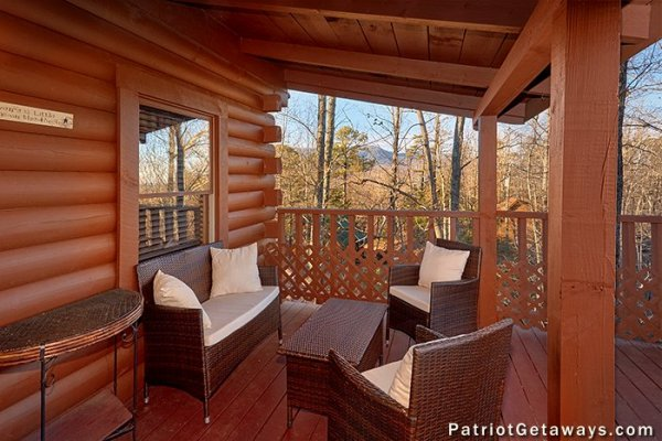 A wicker loveseat, two chairs, and a table on the covered deck at Elevation 1454, a 1-bedroom cabin rental located in Pigeon Forge