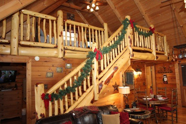 Log banister leading to the loft decorated for christmas at Elevation 1454, a 1-bedroom cabin rental located in Pigeon Forge