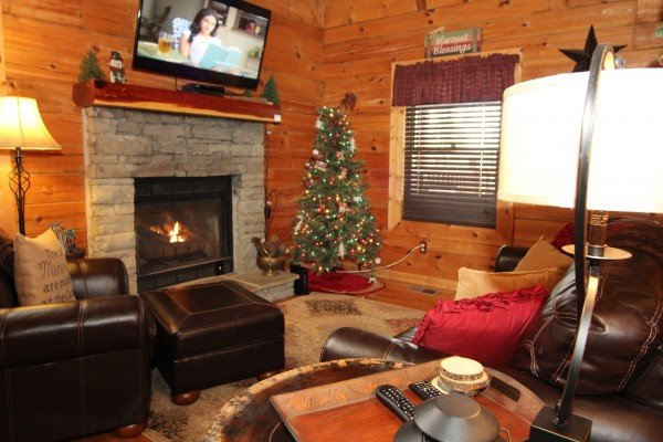 Living room with a Christmas tree at Elevation 1454, a 1-bedroom cabin rental located in Pigeon Forge