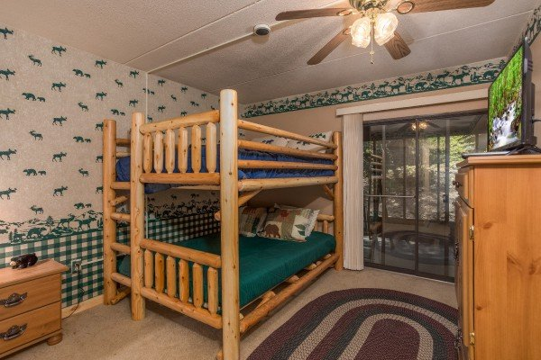 Full size bunk bed and deck access in a bedroom at Under Ober, a 3 bedroom cabin rental located in Gatlinburg