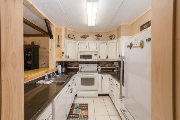 Kitchen with white appliances and white cabinets at Under Ober, a 3 bedroom cabin rental located in Gatlinburg