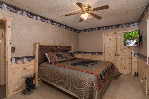 Queen bed and TV in a bedroom at Under Ober, a 3 bedroom rental cabin in Gatlinburg