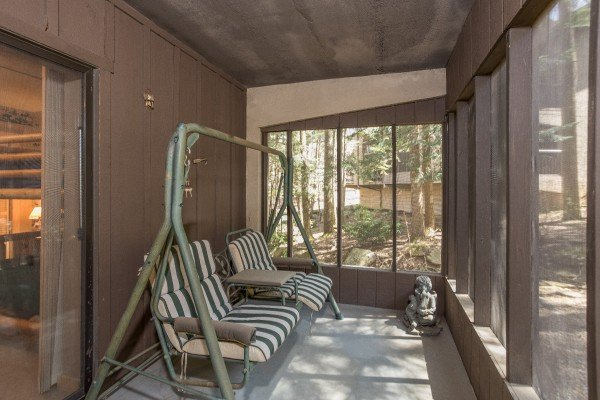 Screened porch with a swing at Under Ober, a 3 bedroom cabin rental located in Gatlinburg