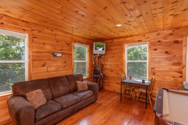 Sofa, checker table, and wall-mounted television at Black Bear Ridge, a 3-bedroom cabin rental located in Pigeon Forge
