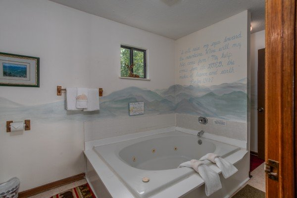 Custom mountain mural behind a jacuzzi at Black Bear Ridge, a 3-bedroom cabin rental located in Pigeon Forge