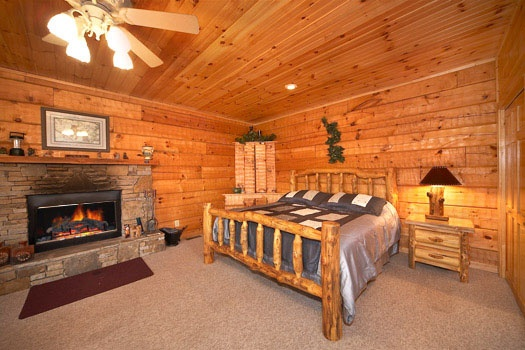 King bed and fireplace at Mountain Memories, a 1 bedroom cabin rental located in Pigeon Forge
