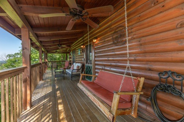 Swing and furniture on a covered porch at Grand View, a 3 bedroom cabin rental located in Sevierville