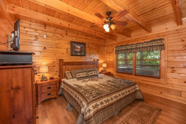King bedroom with nightstand, dresser, and TV at Grand View, a 3 bedroom cabin rental located in Sevierville
