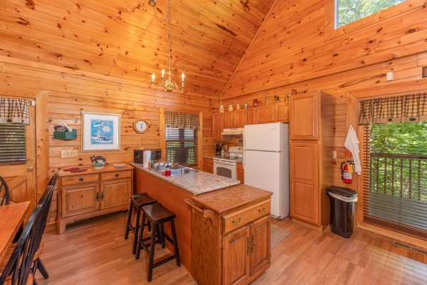 Kitchen with white appliances and breakfast bar at Grand View, a 3 bedroom cabin rental located in Sevierville