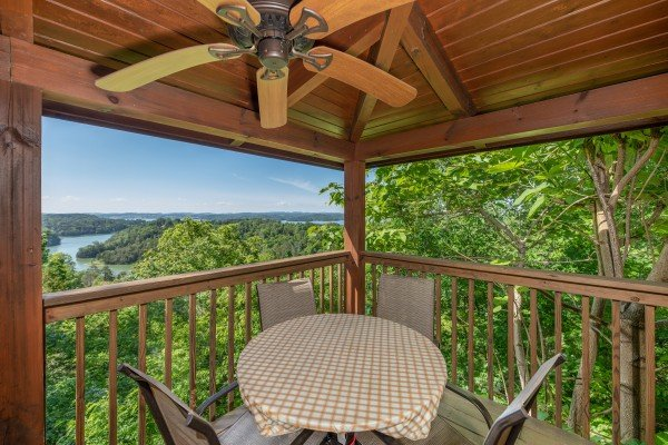 Table for four on a covered deck with a fan and a lake view at Grand View, a 3 bedroom cabin rental located in Sevierville