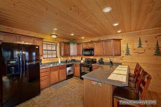 kitchen with bar and barstools at alpine pointe a 5 bedroom cabin rental located in gatlinburg