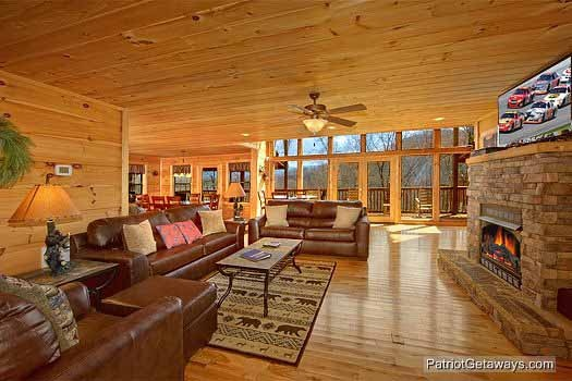 Looking at the sofas in the living room with dining open along the back at Alpine Pointe, a 5 bedroom cabin rental located in Gatlinburg