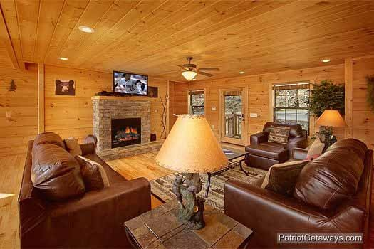 a stone fireplace in the living room with large sofas and chair at alpine pointe a 5 bedroom cabin rental located in gatlinburg