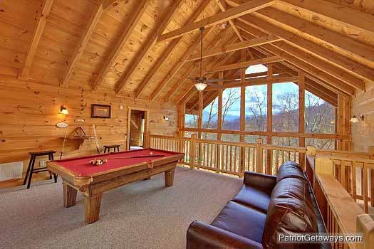 sofa bed and pool table in lofted game room at alpine pointe a 5 bedroom cabin rental located in gatlinburg