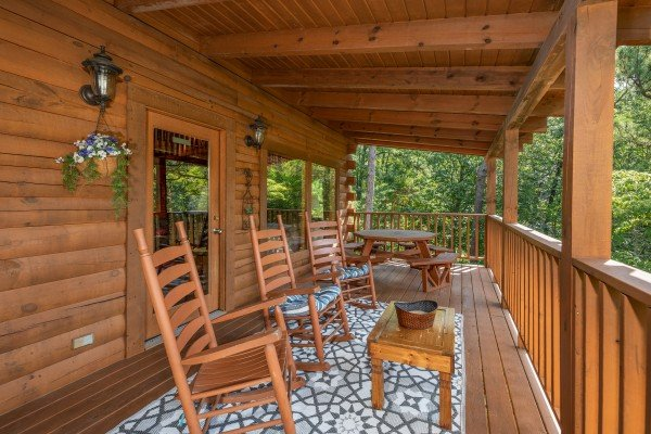Rocking chairs and a picnic table on the covered deck at Majestic Mountain, a 4 bedroom cabin rental located in Pigeon Forge