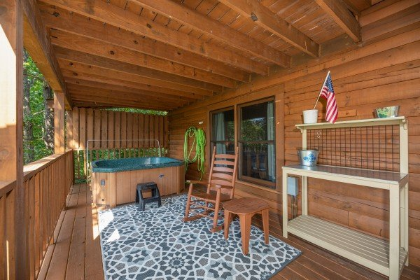 Hot tub, rocking chair, and table on a covered deck at Majestic Mountain, a 4 bedroom cabin rental located in Pigeon Forge