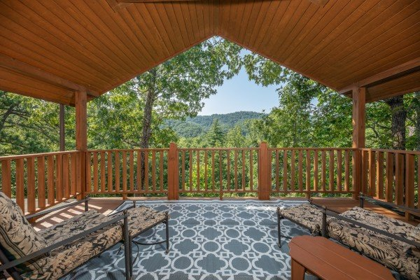 Loft deck with wooded mountain views and chaise lounge chairs at Majestic Mountain, a 4 bedroom cabin rental located in Pigeon Forge