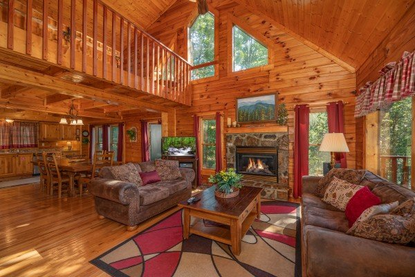 Vaulted living room with fireplace, TV, dining area, and kitchen at Majestic Mountain, a 4 bedroom cabin rental located in Pigeon Forge