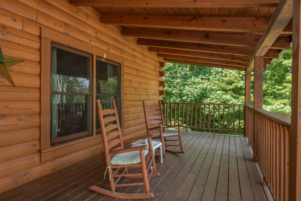 Rocking chairs on a covered deck at Majestic Mountain, a 4 bedroom cabin rental located in Pigeon Forge